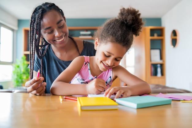 Moeder helpt en ondersteunt haar dochter met homeschool terwijl ze thuis blijft. nieuw normaal levensstijlconcept.