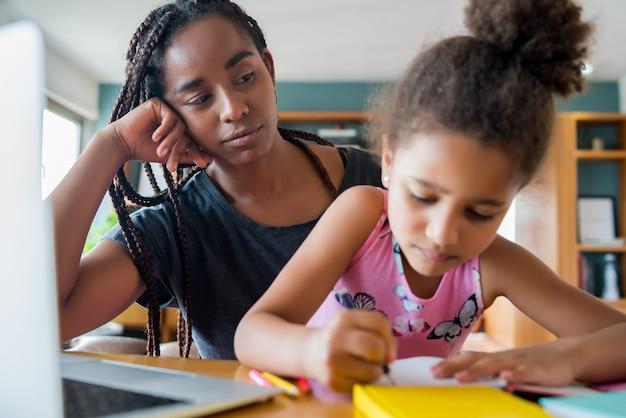Moeder helpt en ondersteunt haar dochter met online school terwijl ze thuis blijft. nieuw normaal levensstijlconcept. monoparentaal concept.