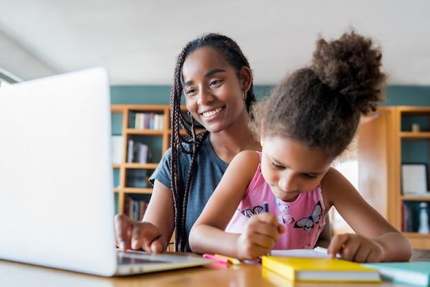 Moeder helpt en ondersteunt haar dochter met online school terwijl ze thuis blijft. nieuw normaal levensstijlconcept