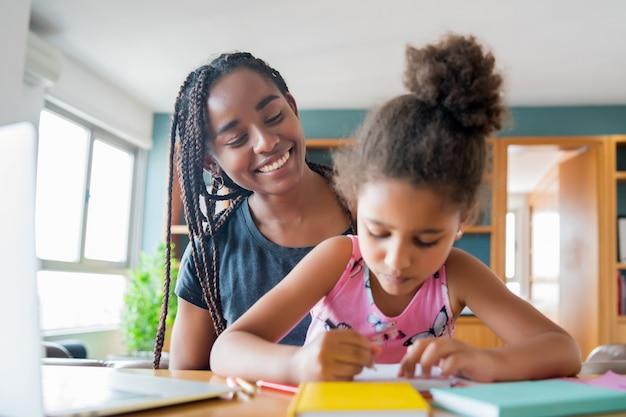Moeder helpt en ondersteunt haar dochter met online school terwijl ze thuis blijft.