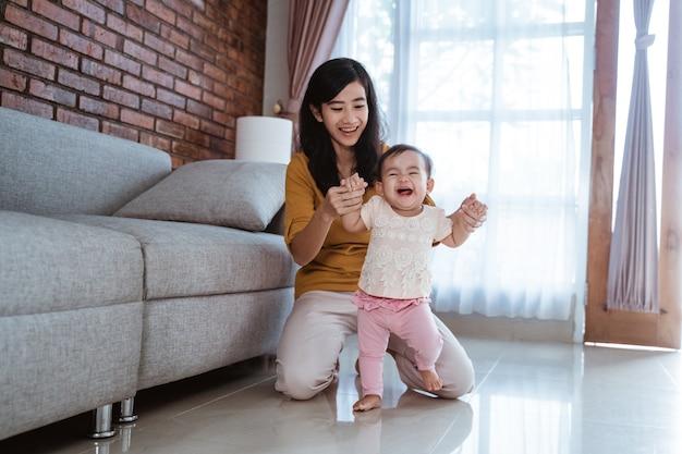 Moeder helpt haar baby om thuis haar eerste stapjes te zetten
