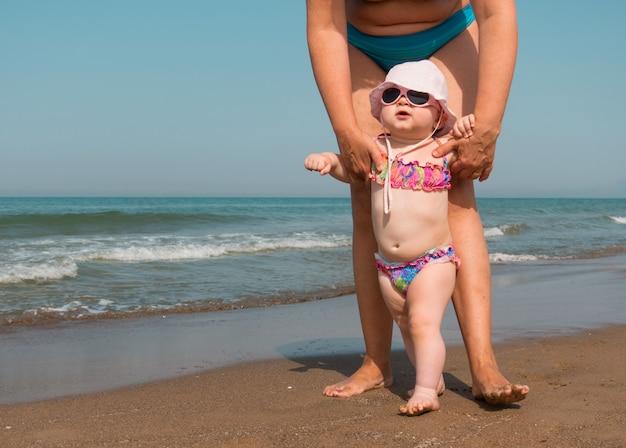 Moeder helpt haar baby staan en lopen op het strand