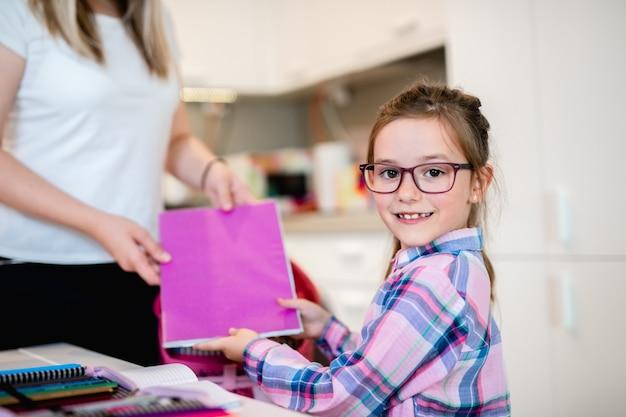 Moeder helpt haar dochter bij het inpakken van schooltas