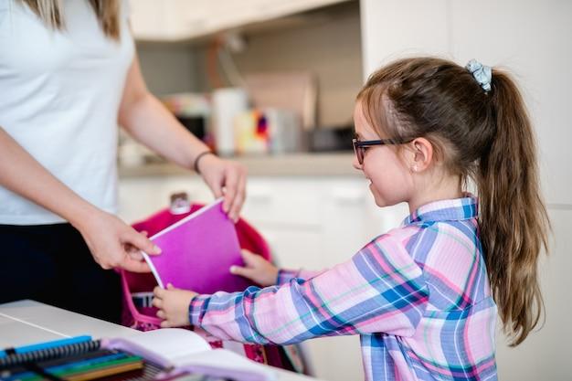 Moeder helpt haar dochter bij het inpakken van schooltas.