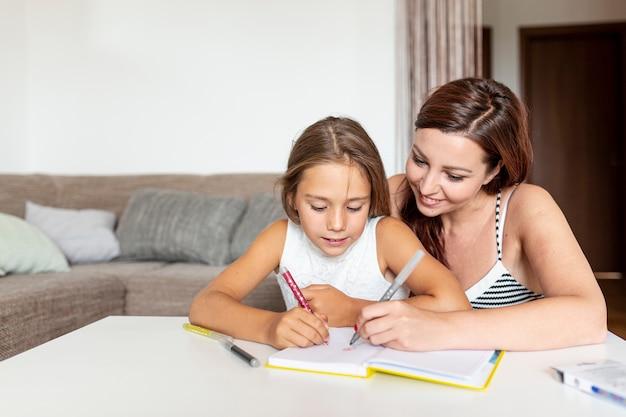 Moeder helpt haar dochter haar huiswerk te maken