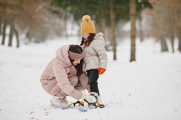 Moeder helpt haar dochter om haar luchten te plaatsen