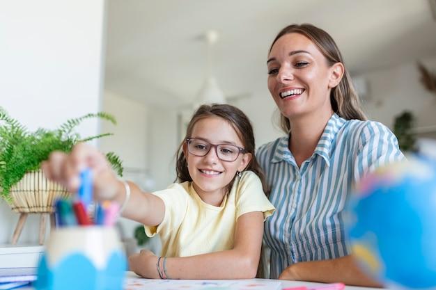 Moeder helpt haar dochter terwijl ze thuis studeert. mooie glimlachende vrouw die schattige dochter helpt thuis schoolwerk te doen