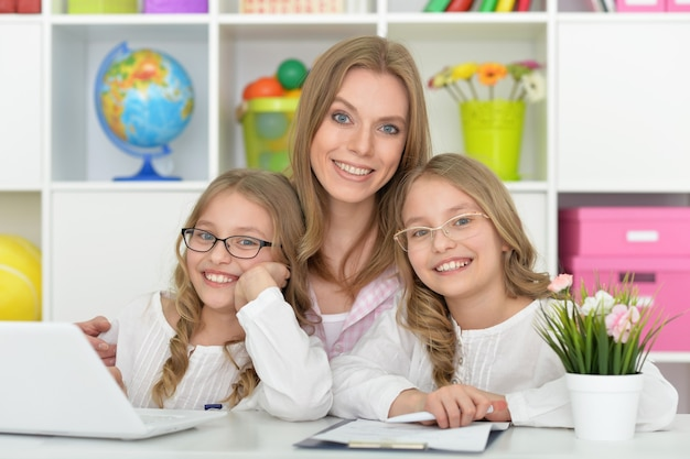 Moeder helpt haar dochters thuis met huiswerk