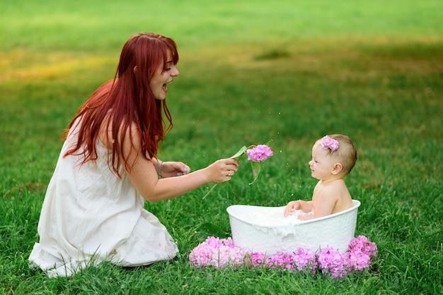 Moeder helpt haar dochtertje van een jaar met baden in de badkamer. gefilmd in een park buiten in de natuur.