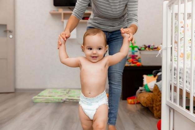 Moeder helpt haar kind om te gaan. de eerste stappen. het kind leert lopen. baby is 11 maanden oud.