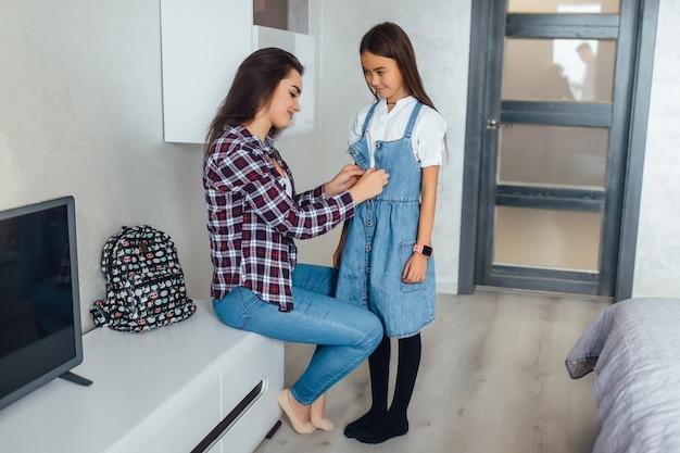 Moeder helpt haar kind 's ochtends voor te bereiden op school, jonge student schooluniform dragen