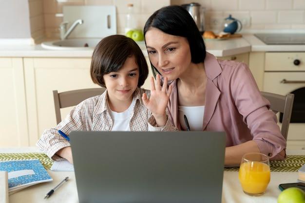 Moeder helpt haar zoon in een online les