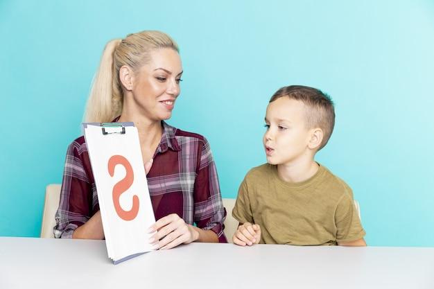 Moeder helpt haar zoon met huiswerk over geïsoleerde roze achtergrond. verre onderwijs.
