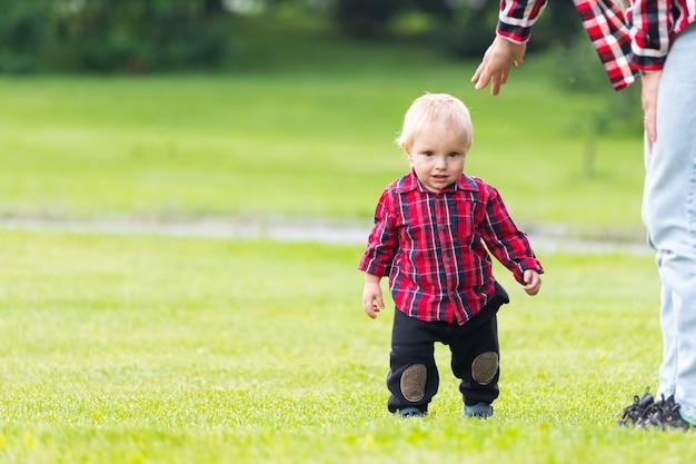Moeder helpt haar zoontje de eerste stappen op het groene veld zetten Premium Foto