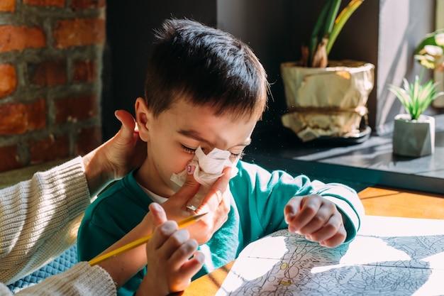 Moeder helpt haar zoontje om zijn neus te snuiten met een servetallergieconcept