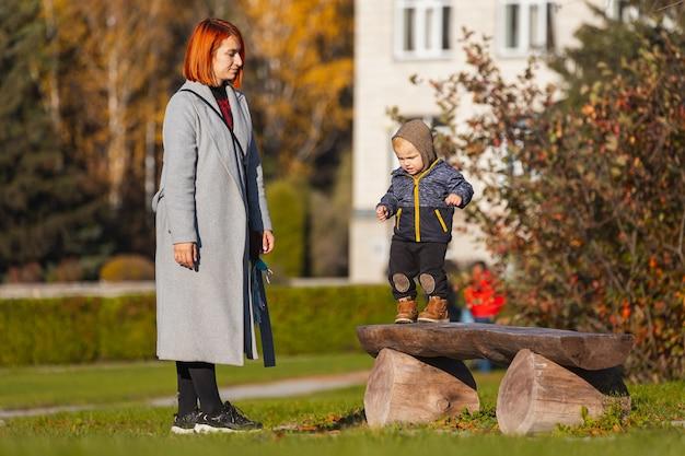 Moeder helpt haar zoontje zijn eerste stapjes te zetten op een houten bankje