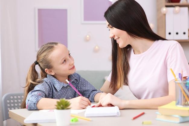 Moeder helpt het meisje om huiswerk te maken kinderen en ouders