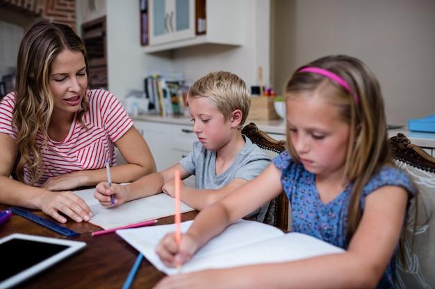 Moeder helpt kinderen met hun huiswerk