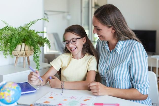 Moeder helpt meisje met huiswerk. moeder en dochter tekenen samen, moeder helpt met huiswerk. schattig meisje doet haar huiswerk op school met zijn moeder, thuis, ze schrijft in een boek