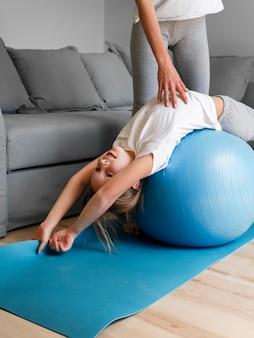Moeder helpt meisje om te trainen met de bal