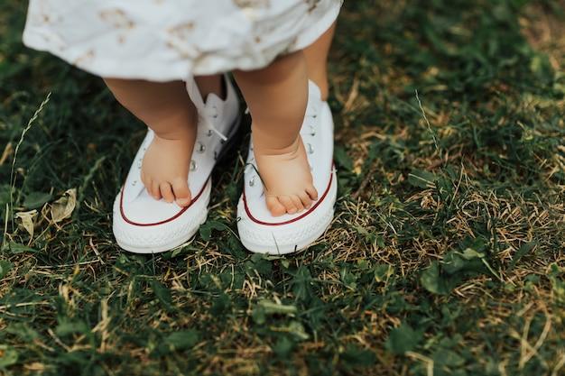 Moeder helpt om de eerste stapjes van het kind op het groene gras te zetten Premium Foto