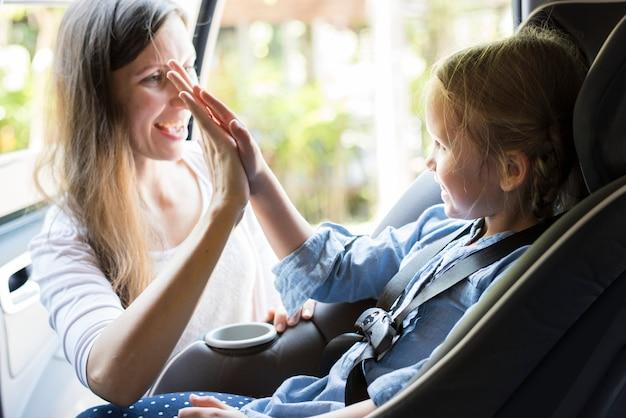 Moeder helpt om de veiligheidsgordel om te doen