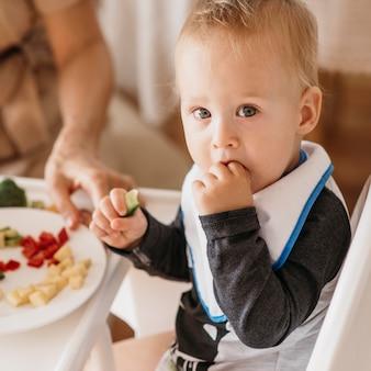 Moeder helpt schattige baby om te kiezen welk voedsel hij wil eten