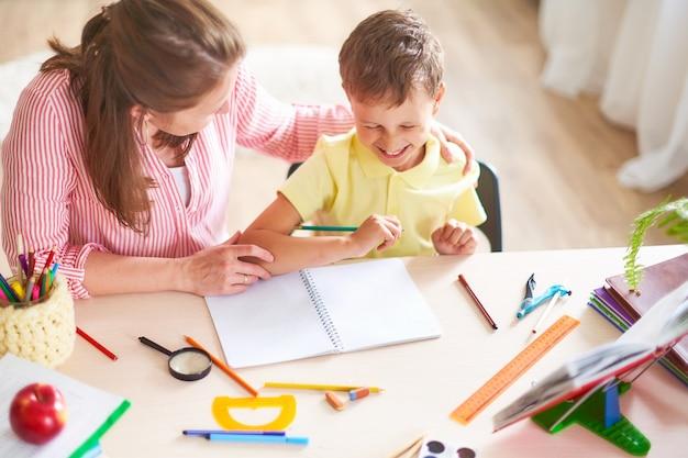 Moeder helpt zoon lessen te volgen.