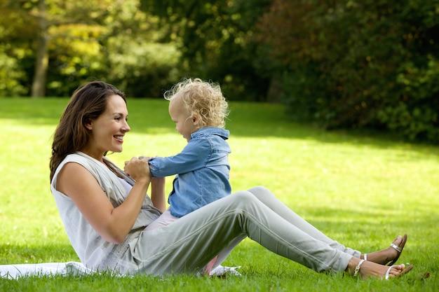 Moeder het spelen met leuke baby in openlucht