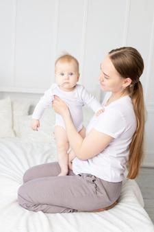 Moeder houdt baby in haar armen en knuffelt hem zachtjes op het witte bed thuis, moeders liefde