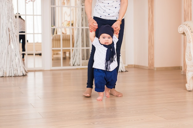 Moeder houdt baby's handen vast om hem te helpen lopen. eerste stap concept.