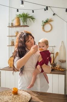 Moeder houdt babymeisje in haar armen en voedt met een lepel. babymeisje kijkt naar de camera