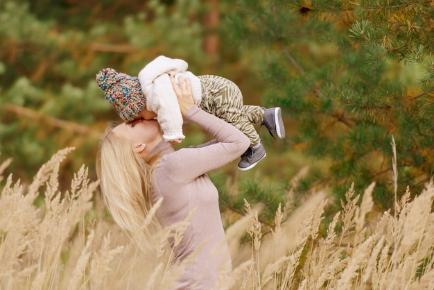 Moeder houdt de baby in haar armen en kust hem in het bos