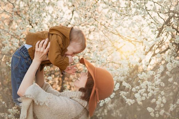Moeder houdt de baby tegen de achtergrond van bloeiende bomen