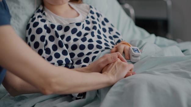 Moeder houdt dochterhanden vast en wacht op medicamenteuze behandeling na ziekte-infectie