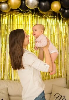 Moeder houdt een babymeisje in haar armen op feestelijke gordijnen met ballonnen