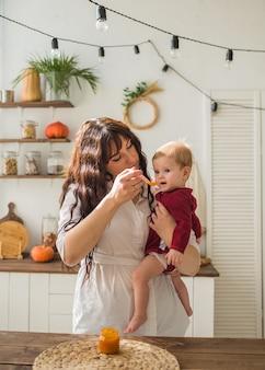 Moeder houdt een babymeisje vast en voert gepureerde wortelpuree in de keuken