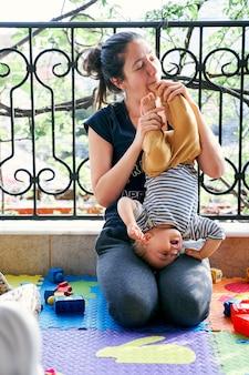 Moeder houdt een klein meisje op haar schoot en bijt in haar voet