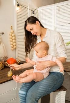 Moeder houdt haar dochter in haar armen en voert aardappelpuree met een lepel op stoel in de keuken