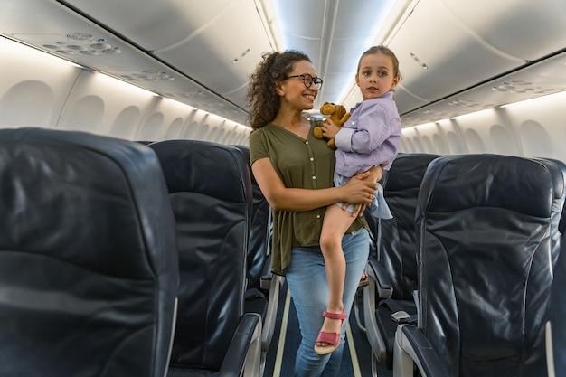 Moeder houdt haar dochter in haar armen in het gangpad bij de stoelen in het vliegtuig