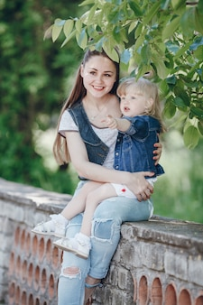 Moeder houdt haar dochter in haar armen, zittend op een stenen balustrade