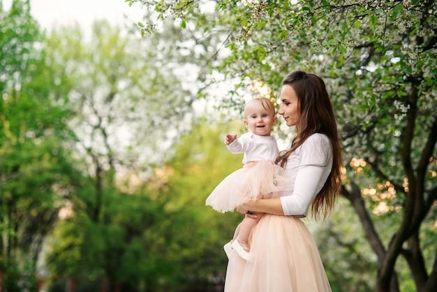 Moeder houdt haar dochtertje in haar armen tussen bloeiende bomen. moeder en haar kleine baby droegen een roze familiekledingjurk.