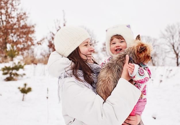 Moeder houdt haar glimlachende dochter en klein hondje op haar handen