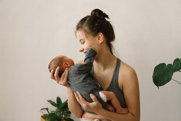 Moeder houdt haar pasgeboren zoontje vast en knuffelt thuis blije baby en moeder