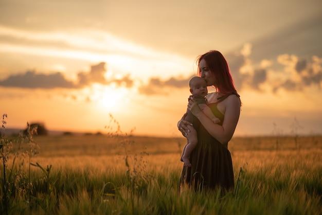 Moeder houdt haar zoon teder in haar armen in een tarweveld