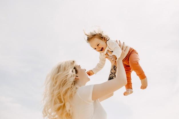 Moeder houdt klein meisje in de armen omhoog op een hemelachtergrond die met haar speelt en lacht