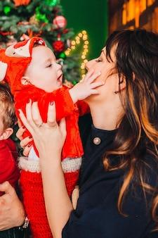 Moeder houdt kleine jongen in rode kerst pak