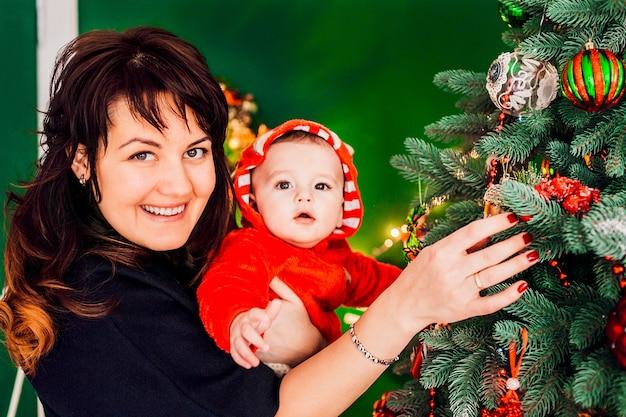 Moeder houdt kleine jongen in rood pak vóór een kerstboom