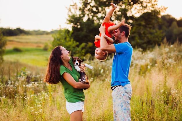 Moeder houdt kleine papaver vast terwijl vader staat met de ondersteboven gekeerde zoon