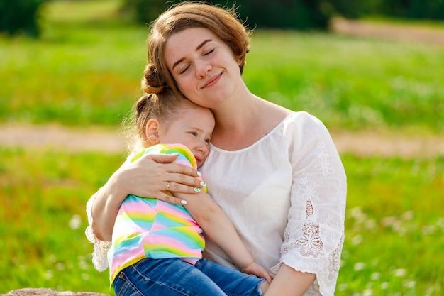 Moeder houdt schudt het meisje in haar armen in de zomer buiten